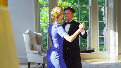 Happy romantic young couple in evening wear dancing together in elegant home