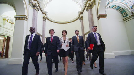 Confident and successful delegates walking through historic conference building