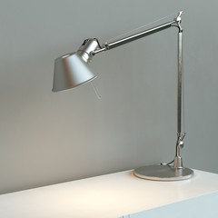 Metal desk lamp stand on white surface behind grey wall