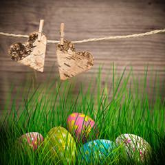 2 Herzen aufgehängt auf einer Leine und Ostereier im Gras