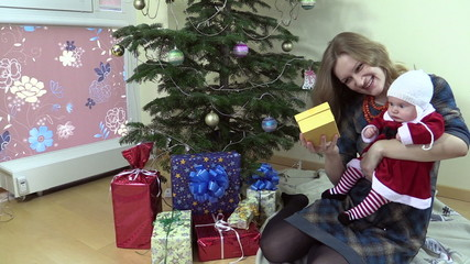 Joyful woman show her lovely baby gift box near Christmas tree