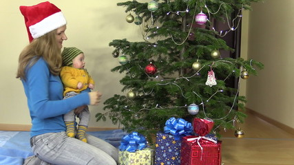 mother with newborn baby in her hands hang Christmas tree toy
