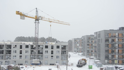Crane lift concrete block house part and workers work in winter