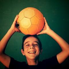 Niño sujetando balón sobre su cabeza