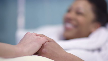 Caring nurse chats with a female patient and holds her hand to offer comfort