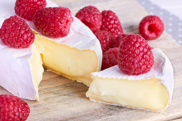 cheeses on wooden background with raspberry