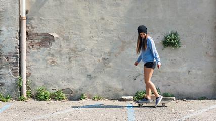 Teenager portrait riding skateboard against scratched concrete w