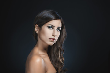 Beauty portrait of attractive brunette woman against dark blue b