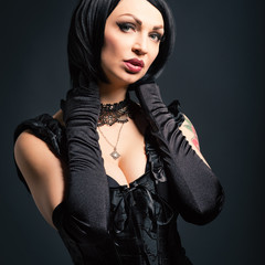Portrait of a busty woman wearing vintage corset and black glove