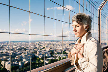 Young blonde woman portrait on top of the Eiffel Tower with city