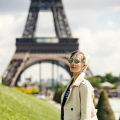 Young blonde woman portrait in front of the Eiffel Tower in Pari