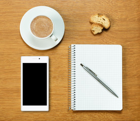 Smartphone, coffee, notepad and pen