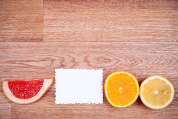 Slices of citrus fruit and white paper on the wooden background
