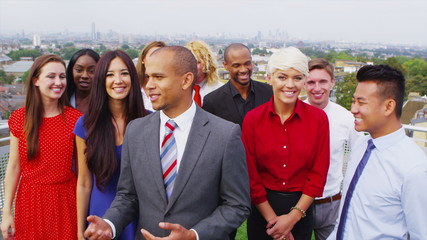 Portrait of attractive smiling business team with city view in the background