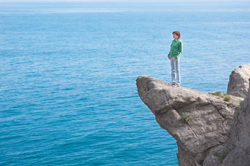 Young slim lonely woman standing at the edge of mountain cliff a