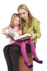 Mother and her lovely daughter sitting, reading a book