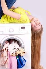 girl lies on a washing machine with the laundry for washing