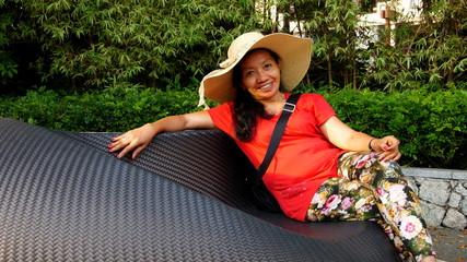 attraktive Indonesierin posiert auf Gartenbank