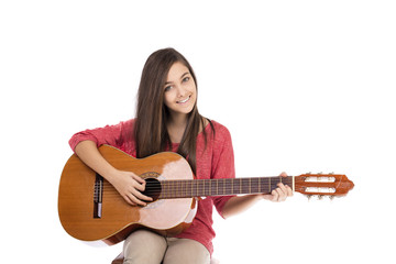 Pretty teenage girl playing an acoustic guitar