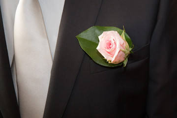 Wedding red rose on a black  suit of the groom