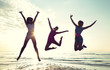 happy female friends dancing and jumping on beach - 80525298