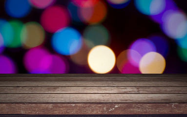 Empty wooden deck table with foliage bokeh background.