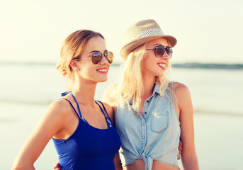 two smiling women in sunglasses on beach