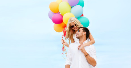 couple with colorful balloons at seaside
