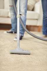 close up of human legs and vacuum cleaner at home