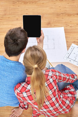close up of couple with tablet pc and blueprints