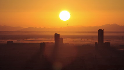 Sunrise in Dubai Marina with buildings and mountains from top of