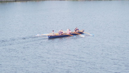 Rowing crew traveling down the River Thames on a sunny day