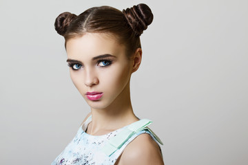 portrait of young woman with makeup and buns