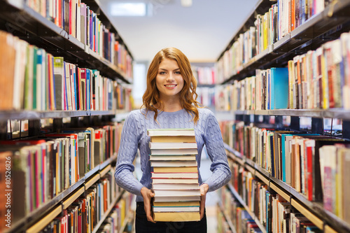 happy student girl or woman with books in library - 80526826
