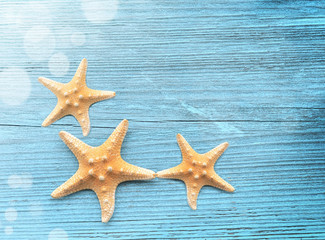 Three starfish on a blue wooden background