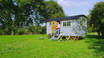 Cheerful senior couple relaxing outside quaint caravan in a natural setting