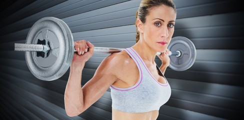 Strong female crossfitter lifting barbell behind head