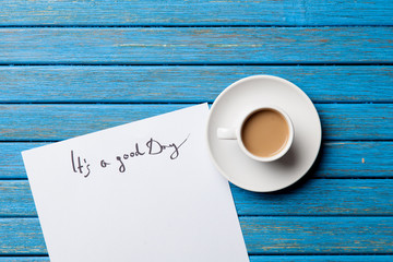 Cup of coffee and inscription on paper