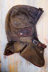leather vintage helmet over wooden background