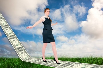 Composite image of businesswoman doing a balancing act