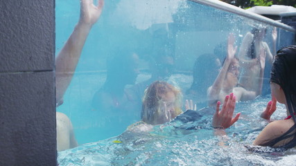 Attractive group of friends enjoy pool party and relaxing in hot tub