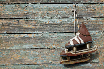 vintage pair of  ice skates hanging on a cracked paint wall