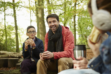 Beech woods in Autumn. Three people, a father and two children having a picnic.