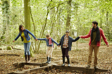 Beech woods in Autumn. A family of four people, two adults and two children.