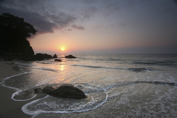 Sunset and a view across a beach and headland in Puerto Vallarta.