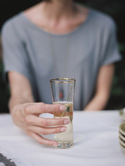 A woman holding a glass of champagne seated at a table.