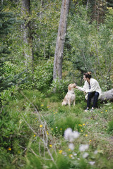 A woman seated on a log patting her retriever dog.