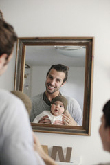 A mother and father with their baby, looking in the mirror.