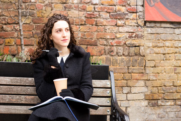 a thoughtful young woman with her diary and a coffee.