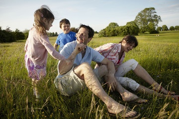A family, two parents and two children outdoors on a summer evening.